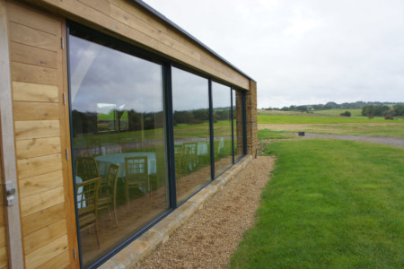 Structural glazing with frameless glass doors and Sky-frame sliding doors.